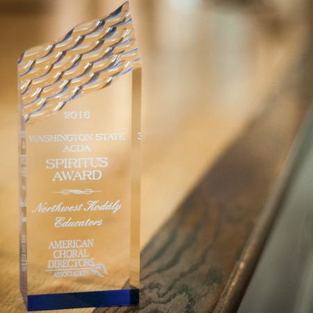 """This image is a picture of the Spiritus Award given to NWKE by Washington State ACDA for our significant contribution to choral music in Washington State. The award is a glass prism with an angled top that has a wavy texture. The text on the award reads """"2018 Washington State ACDA Spiritus Award - Northwest Kodály Educators - American Choral Directors Association."""""""