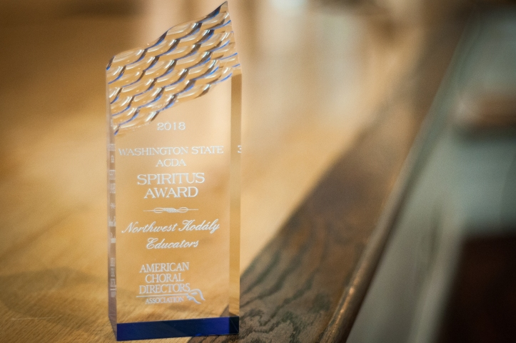"This image is a picture of the Spiritus Award given to NWKE by Washington State ACDA for our significant contribution to choral music in Washington State. The award is a glass prism with an angled top that has a wavy texture. The text on the award reads ""2018 Washington State ACDA Spiritus Award - Northwest Kodály Educators - American Choral Directors Association."""